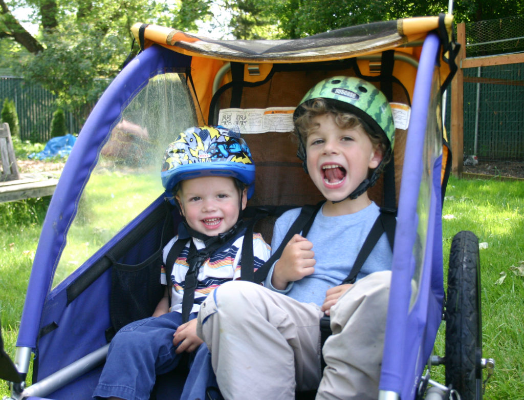 two boys in a bike trailer